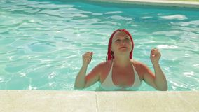 Tanned woman with pigtails dancing in the pool