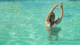 Tanned woman with pigtails dancing in the pool with raised hands