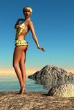 Tanned woman in polka dot yellow swimsuit on beach Royalty Free Stock Photo