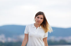 Tanned woman. Portrait of a tanned young woman with long hair in white t-shirt. Mountains on blurred background. Shallow depth of field. Focus on model Royalty Free Stock Photography