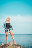 Tanned woman posing at the beach on summer day, looking up. Dreamy female in jeans clothes, standing rocky coast, blue Stock Images