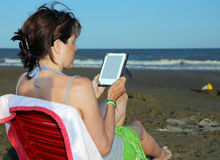 Tanned woman reads the ebook on the seashore Royalty Free Stock Photography