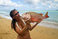 Tanned woman sends a kiss to a huge fish Stock Photo