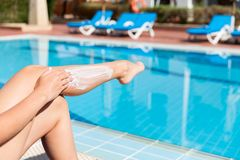 Tanned woman is sitting by the swimming pool and applying sunblock to protect her skin from sunburn. Sun Protection Factor in. Vacation, concept royalty free stock photography