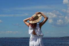 Tanned woman in white dress and hat on riverside. Tanned woman in white dress and glamour hat on riverside, back view, deep blue water on background Royalty Free Stock Photography