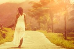 A tanned woman in a white dress walks forward on the road. The view from the back. In the background, a mountain and palm trees. Tint and light. Close up stock photo