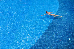 Tanned young europen woman swimming in pool Royalty Free Stock Photography