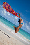 Tanned young europen women with red pareo jump Royalty Free Stock Image
