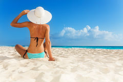 Tanned young girl sitting on the beach Stock Photography
