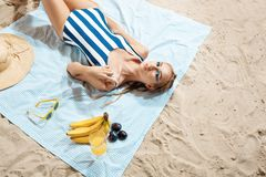 Tanned young woman taking unhealthy sunbath on a summer day on a beach hiding from the sun with straw hat and glasses royalty free stock images