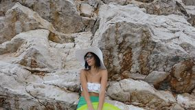 Tanned young woman in white bikini, sunglasses and big hat with mattress near the high rock by the sea. Summer vacation. Summer day, slow motion stock video footage