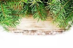 Tannen-Baumaste auf hölzernem Brett mit Schnee Stockbild