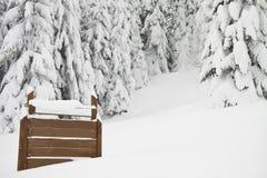 Tannenbäume mit Schnee und einem Zeichen auf dem links, horizontal Stockfotografie