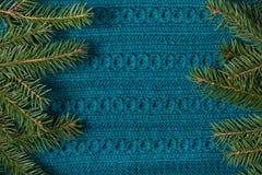 Tannenbaum als Rahmen auf gestricktem Strickjackenhintergrund Weihnachtsniederlassung und -glocken Abstraktes Muster Stockfoto