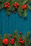 Tannenbaum als Rahmen auf gestricktem Strickjackenhintergrund Weihnachtsniederlassung und -glocken Abstraktes Muster Flache Lage Stockfotos