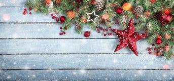 Tannenbaum und -stern auf hölzernem Hintergrund mit Schneeflocken Lizenzfreie Stockfotografie