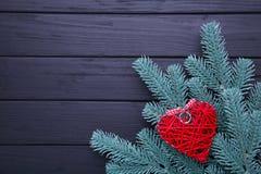 Tannenbaumast mit einem roten Herzen auf hölzernem Hintergrund lizenzfreie stockfotos