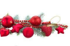Tannenbaumast und rote Weihnachtsdekorationen Stockfotografie