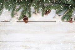 Tannenblätter und Kiefernkegel, die rustikale Elemente auf weißer hölzerner Tabelle mit Schneeflocke verzieren stockfotografie