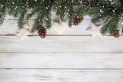 Tannenblätter und Kiefernkegel, die rustikale Elemente auf weißer hölzerner Tabelle mit Schneeflocke verzieren Lizenzfreie Stockfotos