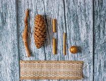 Tannenzapfen, Stöcke und Vergoldungsstöcke und Nuss und festliches Band auf einem Hintergrund von grauen hölzernen alten Brettern Lizenzfreies Stockbild