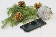Tannenzweig mit Goldkegeln, -spielwaren und -Handy auf einem Holztisch Stockfoto