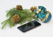 Tannenzweig mit Goldkegeln, -spielwaren und -Handy auf einem Holztisch Stockbilder