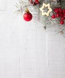 Tannenzweig mit Weihnachtsdekorationen auf der weißen hölzernen Planke Stockfoto