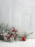 Tannenzweig mit Weihnachtsdekorationen auf hölzerner Planke Lizenzfreie Stockbilder