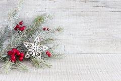 Tannenzweig mit Weihnachtsdekorationen auf weißem rustikalem hölzernem Hintergrund Stockfotos