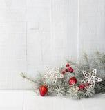 Tannenzweig mit Weihnachtsdekorationen auf weißem rustikalem hölzernem Hintergrund Stockfotografie