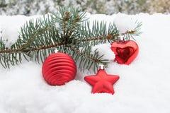 Tannenzweig mit Weihnachtsspielwaren im Schnee Lizenzfreies Stockfoto