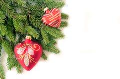 Tannenzweige und Lichthintergrund mit zwei roter Weihnachtsspielwaren Ionen lizenzfreie stockfotos