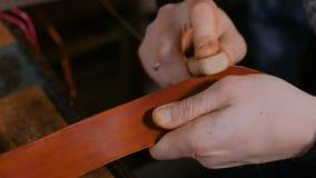 Скиннер работая с кожаным поясом акции видеоматериалы
