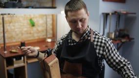 Tanneur masculin dans son studio travaillant à la production de la ceinture en cuir Artisan en cuir de marchandises au travail da banque de vidéos