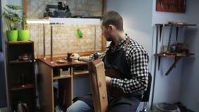 Tanneur masculin dans son studio travaillant à la production de la ceinture en cuir La phase finale, un homme avec une aiguille e banque de vidéos