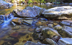Tannin colored mountain stream and rocks. In early spring on a sunny day royalty free stock photos