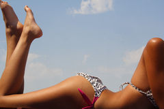 Tanning. Girl in bikini tanning in the bright summer sun Royalty Free Stock Photos
