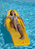 Tanning. Young woman lying in the sun on a floating mattress royalty free stock image