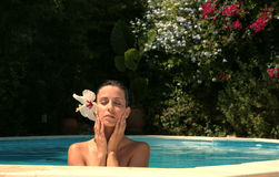 Tanning. Young woman in spa resort in the pool while tanning royalty free stock images