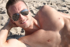 Tanning at the beach. Handsome blond man lying on the sand Stock Photography