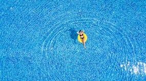 Tanning em uma associação A mulher relaxa na associação no dia ensolarado no anel inflável amarelo imagem de stock