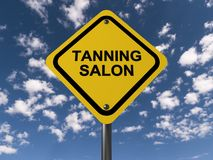 Tanning salon. Yellow diamond shaped highway style sign with text 'tanning salon' in black uppercase letters and behind blue sky and fluffy white cloud Royalty Free Stock Photos