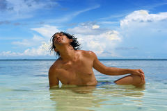 Tanning in sea on tropical beach. Asian male teenager soaking and laying in a tropical sea near the beach, tanning, sun worshiping and enjoying his leisure with Stock Photos