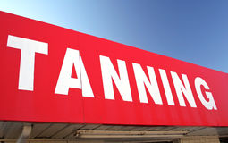 Tanning Sign on Convenience Store. With Blue Sky Royalty Free Stock Image