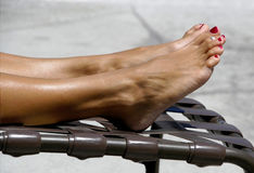 Tanning Toes. Legs and feet of a woman getting a tan on a lounge chair Royalty Free Stock Photography