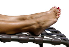 Tanning Toes - isolated. Legs and feet of a woman getting a tan on a lounge chair.  Isolated Royalty Free Stock Photo