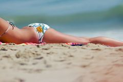 Tanning Woman. Girl in bikini tanning at the beach stock photography
