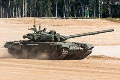 Tanque das forças armadas ou de exército pronto para atacar e movendo-se sobre um terreno abandonado do campo de batalha imagens de stock royalty free