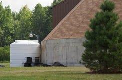 Tanque de armazenamento ao lado do edifício imagem de stock